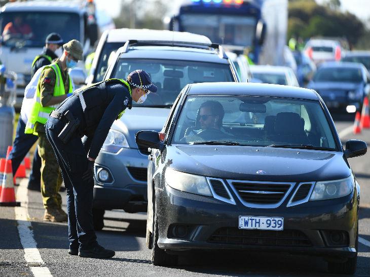 ऑस्ट्रेलिया के विक्टोरिया में दूसरे राज्यों से आने वाले लोगों से उनकी ट्रैवल हिस्ट्री के बारे में पूछताछ करता एक सुरक्षाकर्मी।