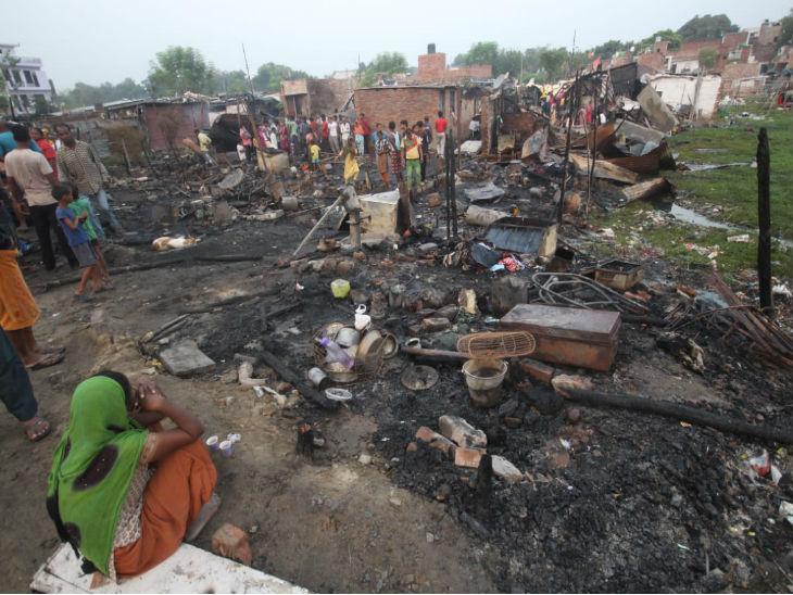 जलकर राख हुई गृहस्थी को देखती महिला।