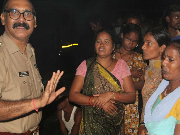 महिलाओं को समझाता पुलिस अफसर।