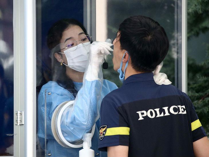 साउथ कोरिया के सियोल स्थित एक लैब में एक युवक का स्वैब सैंपल लेती मेडिकल स्टाफ।