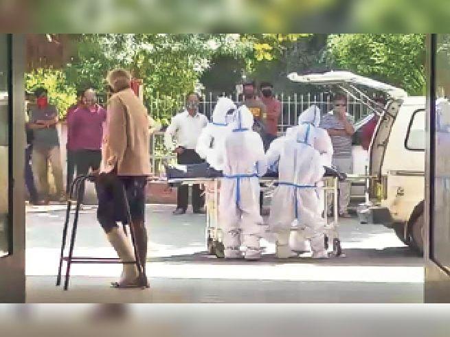संक्रमित शव को एंबुलेंस में रखने के दौरान भी लोग पास में ही खड़े रहे।