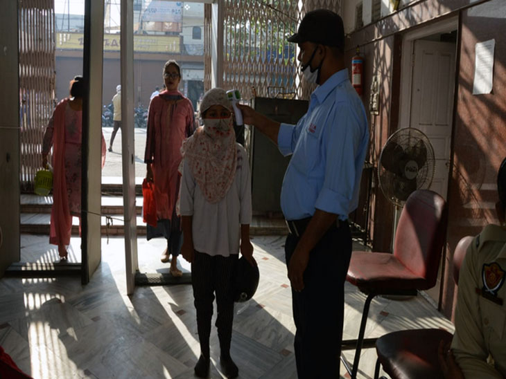 जालंधर के एक प्रमुख दुर्गा माता मंदिर में पूजा के लिए आए श्रद्धालुओं की थर्मल स्क्रीनिंग करता मंदिर प्रबंधन कमेटी तरफ से तैनात सुरक्षाकर्मी।