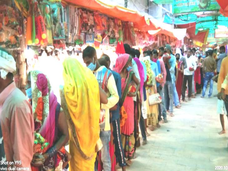 मंदिर में आने वाले श्रद्धालु बाहर सजी दुकानों से खरीददारी करते हुए।