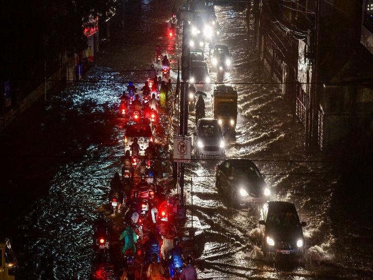 शनिवार रात हुई भारी बारिश के बाद हैदराबाद की पानी से भरी एक सड़क से गुजरती गाड़ियां।