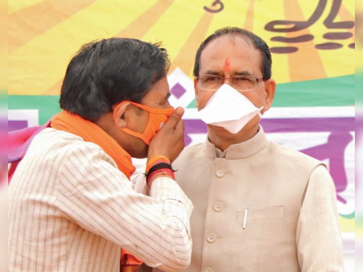 Saying something in the ears of BJP candidate Suresh Rathkheda Shivraj Singh Chauhan on the stage during the meeting of Chief Minister Shivraj Singh Chauhan in Pohri's camp.