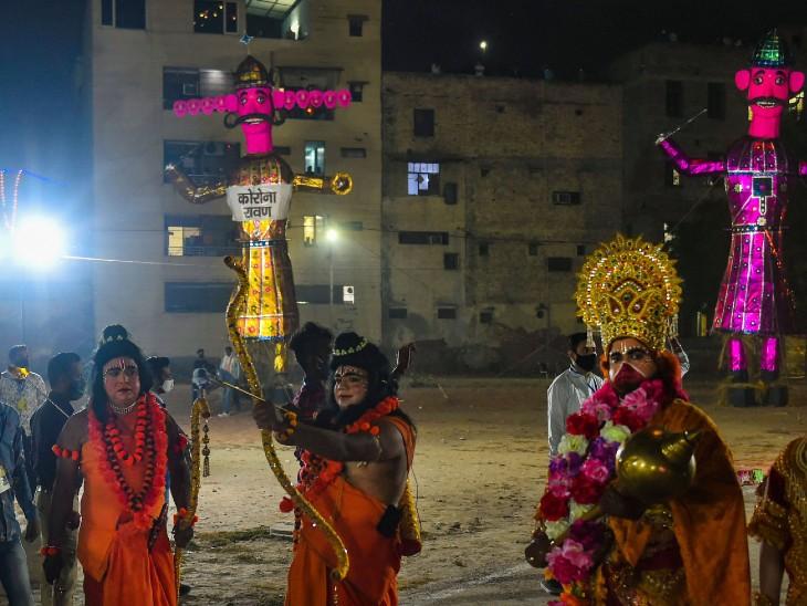 फोटो दिल्ली की है। इस बार यहां रावण को कोरोना का रूप दिया गया है। राम का रूप धारण करके कलाकार ने रावण वध का मंचन किया।