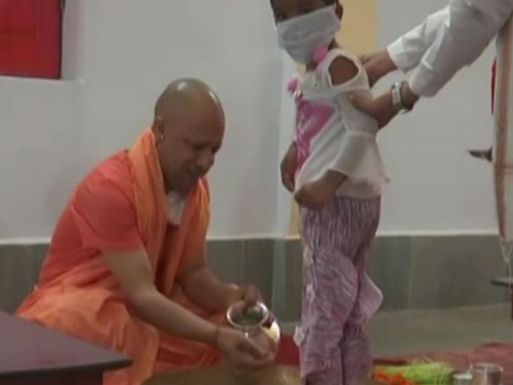 कन्याओं का पांव धोते सीएम योगी।