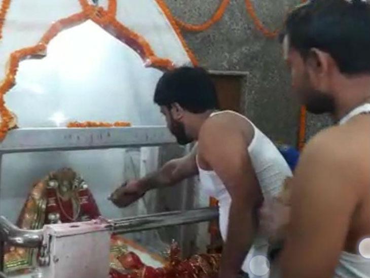 मंदिर में पूजा पाठ करते भक्त।