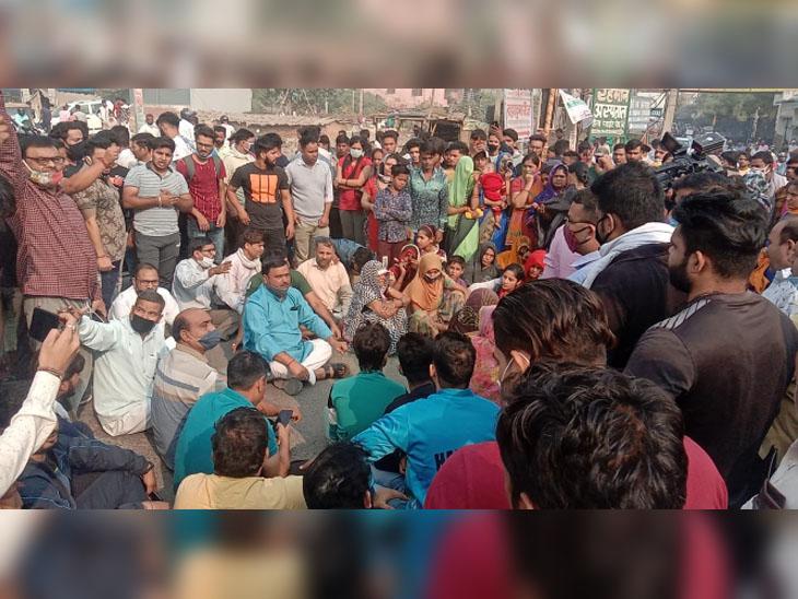 बल्लभगढ़-सोहना रोड पर रोड जाम के दौरान धरने पर बैठे निकिता के परिजन और अन्य लोगों की भीड़। पीछे जाम में फंंसे वाहन भी दिखाई दे रहे हैं।