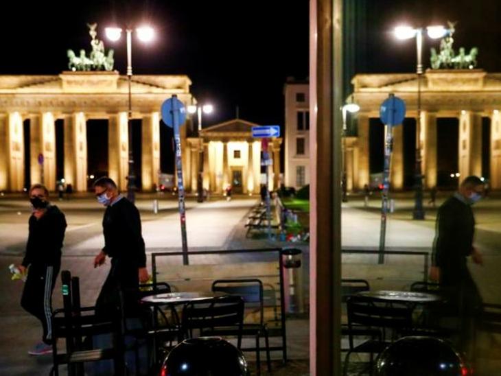 बुधवार को जर्मनी के बर्लिन में एक रेस्टोरेंट के बाहर से गुजरते लोग। यहां आंशिक लॉकडाउन लगाया गया था। अब खबर है कि सरकार इसे सख्त लॉकडाउन में बदल सकती है।