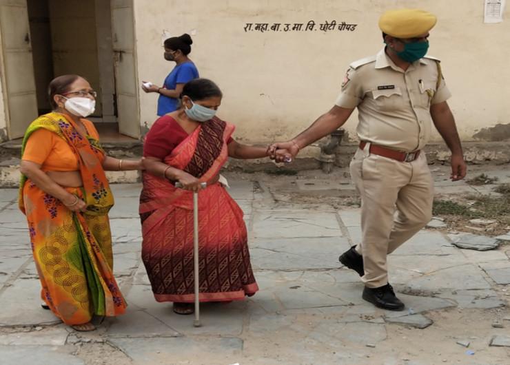 बुजुर्ग महिला मतदाता का हाथ पकड़कर बूथ तक लेकर जाता पुलिसकर्मी