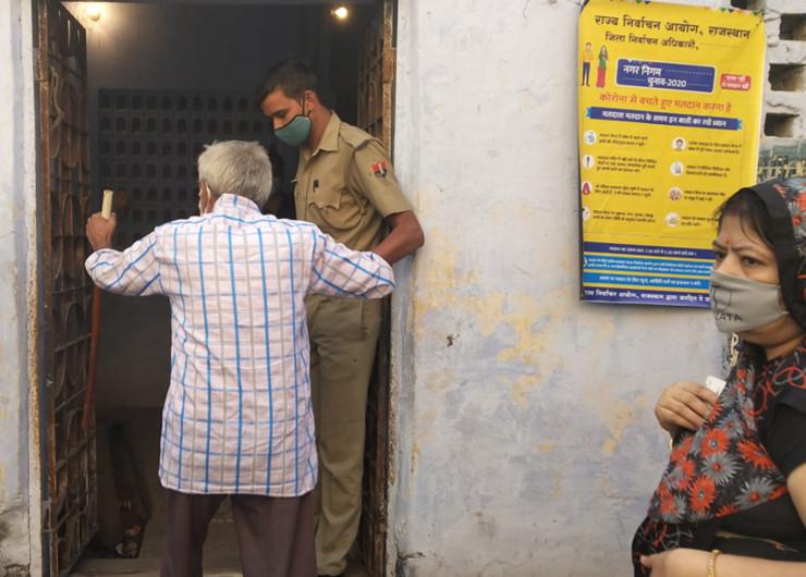 एक पोलिंग बूथ पर बुजुर्ग मतदाता मतदान कक्ष तक पहुंचने के लिए रैंप पर चढ़ने में मदद करता पुलिसकर्मी