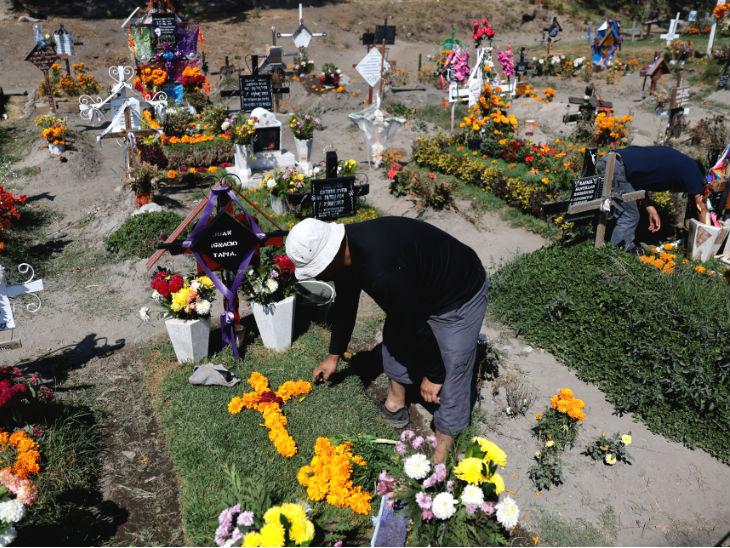 मैक्सिको में रविवार को डेड डे सेलिब्रेट (मृतकों के लिए उत्सव) किया गया। इस दौरान राजधानी मैक्सिको सिटी के एक ग्रेवयार्ड में पिता की कब्र पर फूल चढ़ाता व्यक्ति।