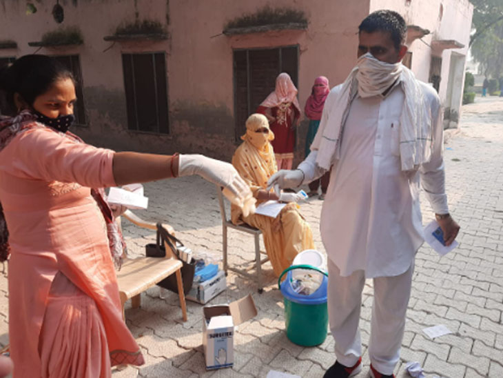 Women employees of electoral staff getting their hands sanitized at polling booth.