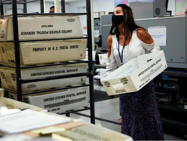 फ्लोरिडा के डोरल में पोस्टल बैलट को काउंटिंग से पहले अरेंज करती इलेक्शन सुपरवाइजर।