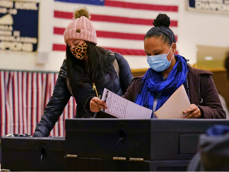 बुधवार तड़के न्यू हैम्पशायर के विंडहैम में वोटिंग करतीं दो महिलाएं। यहां वोटिंग के लिए मास्क मेंडेटरी था।