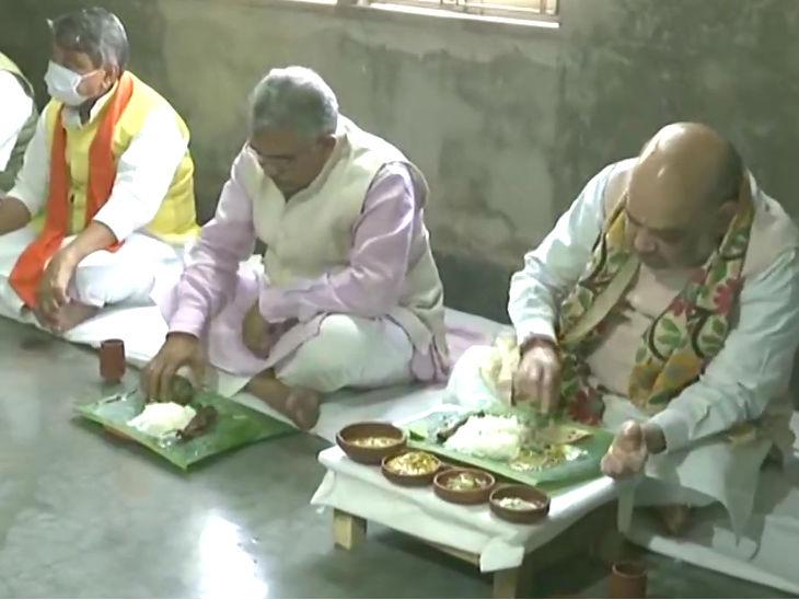 शाह और भाजपा के दूसरे नेता मतुआ समुदाय के घर में खाना खाते हुए।