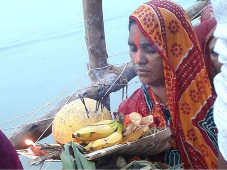 पटना के एक घाट पर छठी मइया को अर्पित करने के लिए सूप में ठेकुआ, फल और कसार सजाए महिला।