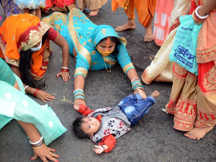 कोलकाता के दोही घाट पर बच्चे के साथ पूजा करने पहुंची महिला।