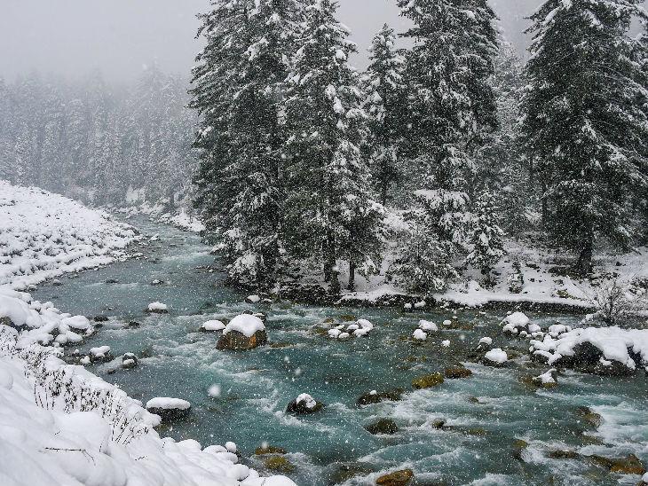 बुधवार की फोटो जम्मू-कश्मीर के गांदरबल जिले के गगनगिर इलाके में बर्फ से ढकी घाटी के बीच से बहती सिंधु नदी की है।
