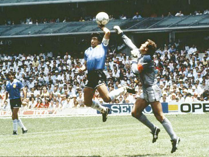 मैराडोना को रोकते इंग्लैंड के गोलकीपर पीटर शिल्टन, पर वे नाकाम रहे। हैंड ऑफ गॉड से गोल हो गया।