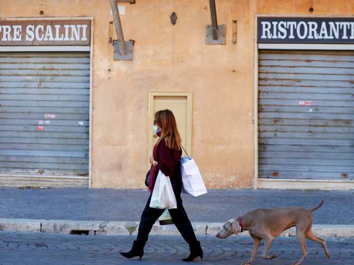 इटली के एक बंद पड़े बाजार से गुजरती महिला। इटली सरकार ने देश के पांच क्षेत्रों में संक्रमण कम होने के बाद प्रतिबंधों में ढील का ऐलान किया है।