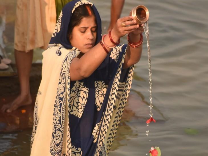 कार्तिक पूर्णिमा पर जल अर्पित करती महिला।