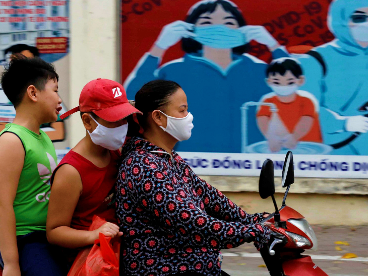 वियतनाम के हनोई शहर में सोमवार को स्कूटर पर जाते लोग। देश में तीन महीने बाद स्थानीय संक्रमण का पहला मामला सामने आया है। संक्रमित हो चि मिन्ह सिटी में पाया गया है।