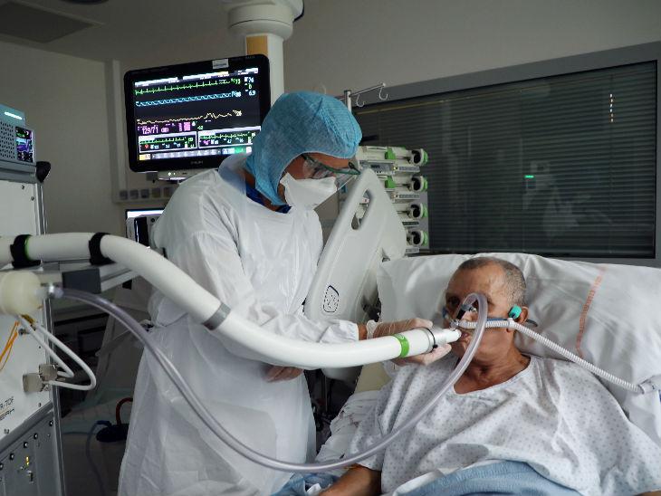 फ्रांस की राजधानी पेरिस के एक अस्पताल में कोरोना संक्रमित व्यक्ति के मेडिकल इक्विपमेंट की जांच करते डॉक्टर।