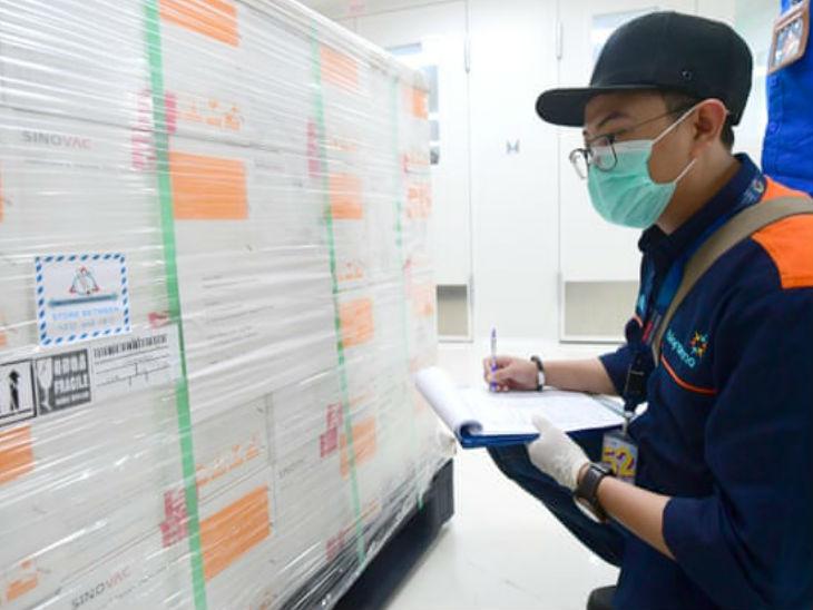 इंडोनेशिया के वेस्ट जावा में रविवार को चीन से पहुंचे कोरोना वैक्सीन की जरूरी जानकारी नोट करता एक कर्मचारी।