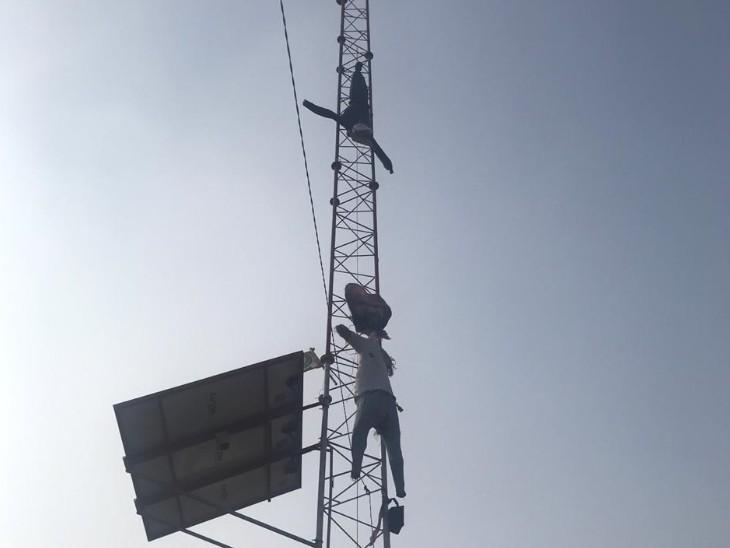 दिल्ली में टावर पर मोदी का पुतला लटकाते हुए प्रदर्शनकारी।