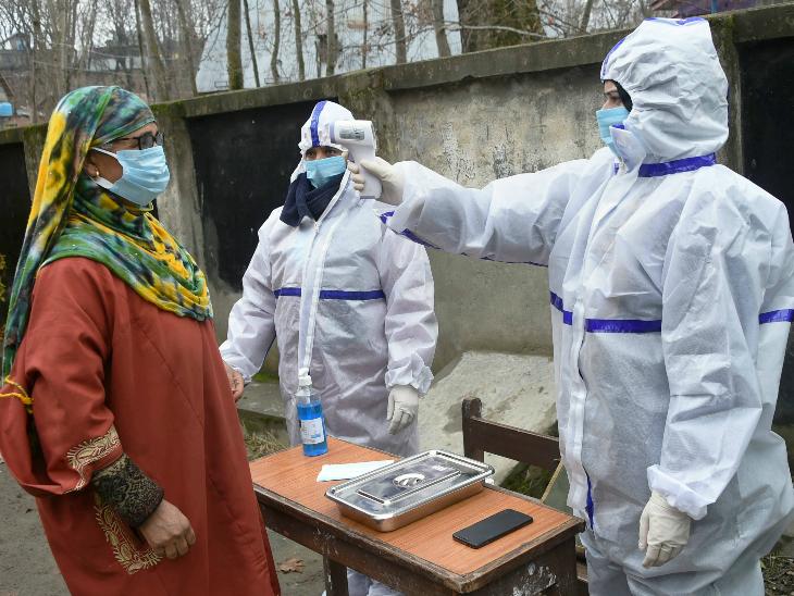 जम्मू-कश्मीर में गुरुवार को DDC चुनाव के 5वें चरण की वोटिंग के दौरान गंदेरबल में कोरोना प्रोटोकॉल के तहत मतदाताओं का टेम्परेचर चेक करते पीपीई किट पहने हुए चुनावकर्मी। - Dainik Bhaskar