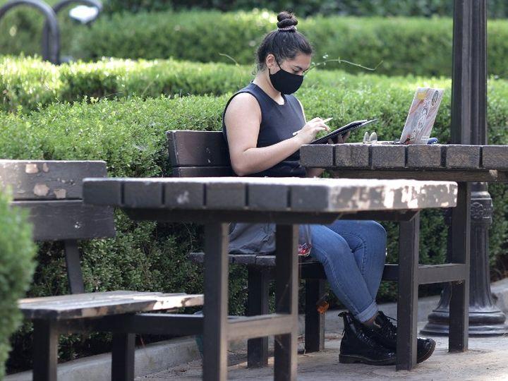 अमेरिका के कैलिफोर्निया में एक अस्पताल के बाहर मास्क लगाकर बैठी महिला।