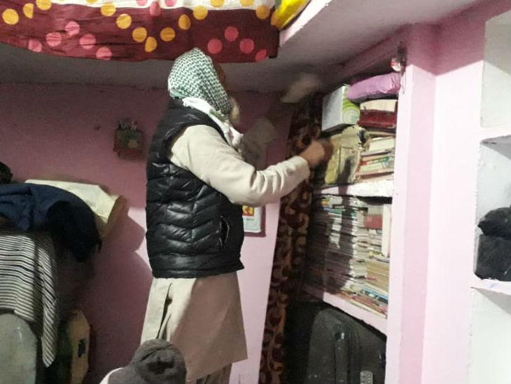 किताबों पर जमा धूल हटाते सुलेमान के पिता।