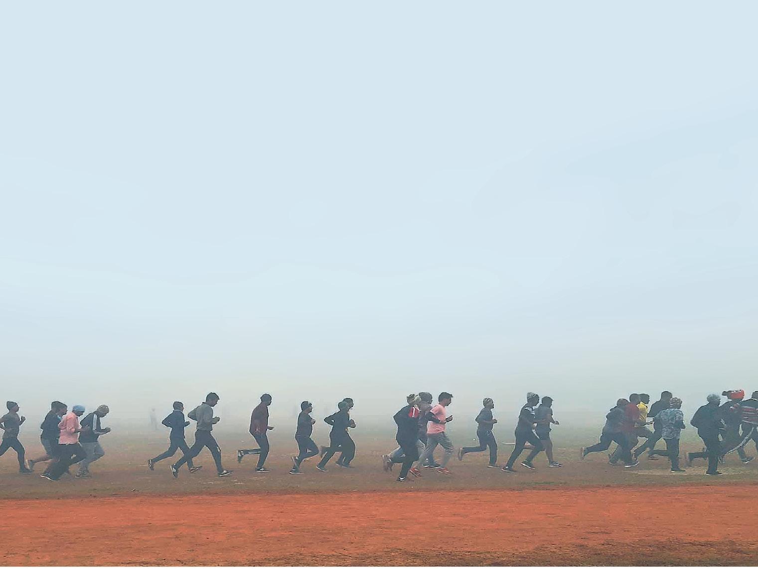 पटना के गांधी मैदान में सेना भर्ती के लिए सुबह के समय दौड़ लगाते युवा।