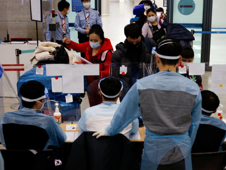 साउथ कोरिया में कोरोना का नया स्ट्रेन मिलने के बाद इंचयोन इंटरनेशनल एयरपोर्ट पर पैसेंजर्स की जांच करते एयरपोर्ट के कर्मचारी।