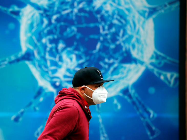A person in front of a corona billboard in a London market.  In Britain, more than 50 thousand infected were found in a single day on Wednesday.  About one lakh people have been vaccinated.