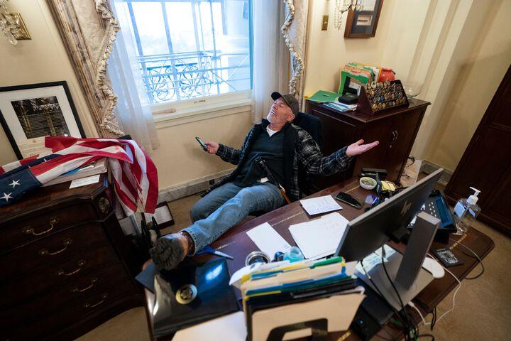 एक शख्स हाउस चैंबर के स्पीकर नैंसी पेलोसी के ऑफिस में मेज पर पैर रखकर उनकी कुर्सी पर बैठा नजर आया।