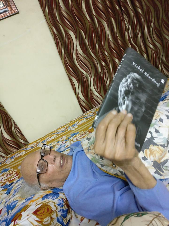 डॉ. बशीर बद्र बिस्तर पर लेटे हुए किताब पढ़ते हुए।