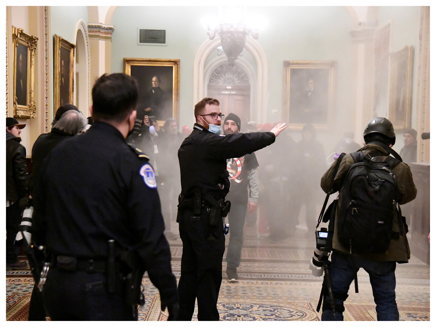 सुरक्षा घेरा तोड़ने के बाद ट्रंप समर्थकों से शांत रहने की अपील करता सुरक्षाकर्मी।