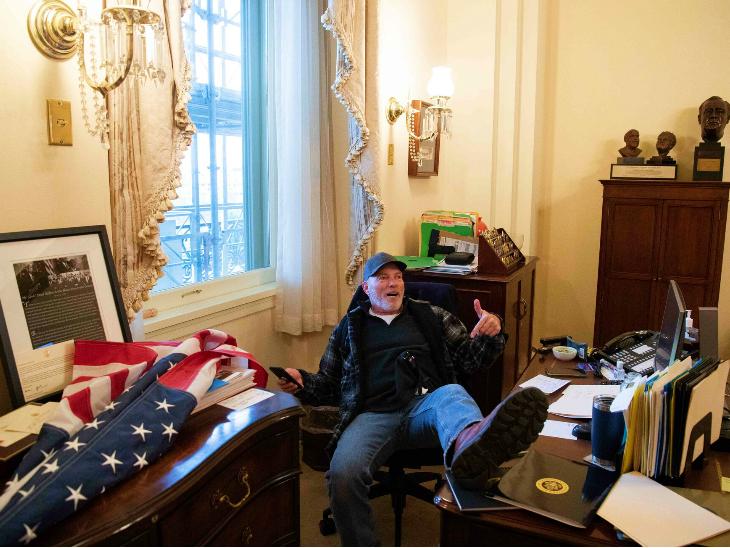 संसद भवन के एक ऑफिस में ट्रम्प का समर्थक रिपब्लिकन पार्टी का झंडा लेकर घुसा और इस तरह एक कुर्सी पर बैठ गया।