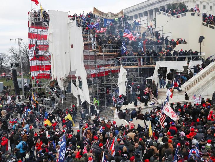 कुछ समर्थक यूएस कैपिटल बिल्डिंग के बाजू में पाइप से बने अस्थायी ढांचे पर चढ़ गए। उस ढंके कपड़े को फाड़ दिया।