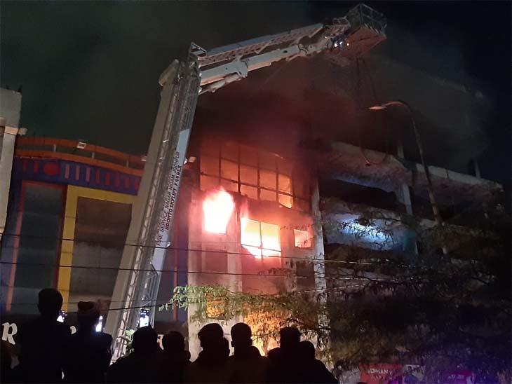 चार मंजिला शोरूम से उठती आग की लपटें।