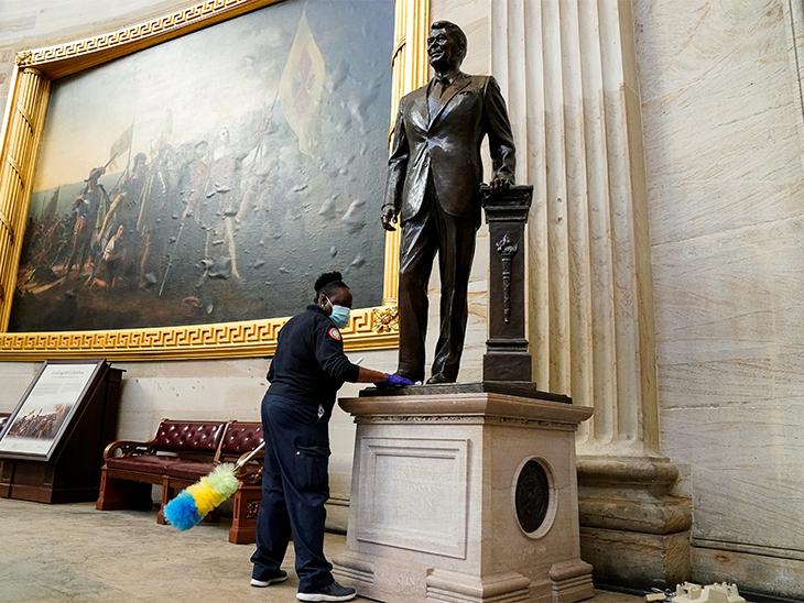 कर्मचारी US Capitol के रोटुंडा में लगी पूर्व राष्ट्रपति रोनाल्ड रीगन के स्टैच्यू को साफ करते हुए। ट्रम्प समर्थकों ने इस स्टैच्यू को भी नुकसान पहुंचाया था।