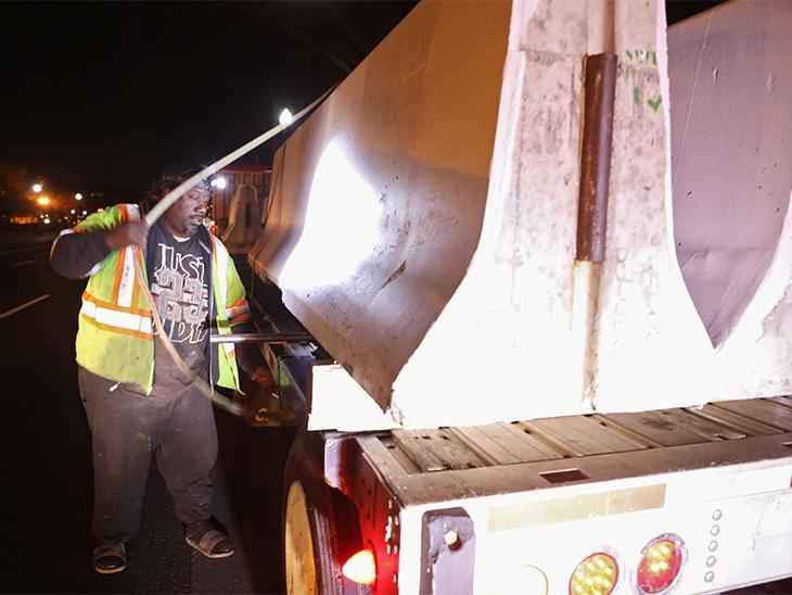 ड्राइवर कॉन्क्रीट बैरियर ट्रक में लोड करते हुए। US Capital में हुई हिंसा के बाद पुलिस को काफी मुश्किलों का सामना करना पड़ा।