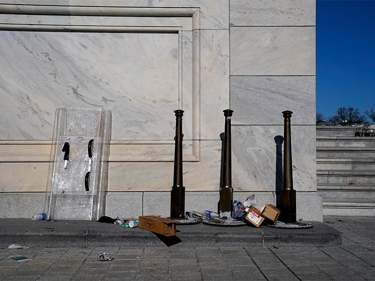 US Capitol में ट्रम्प समर्थकों की ओर से की गई हिंसा के अगले दिन यहां दीवार पर पुलिस की ढाल टिकी हुई नजर आई। इसके बाजू में कुछ टूट-फूट की निशानियां नजर आ रही हैं।