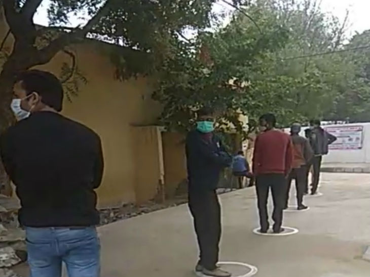 वैक्सीन लगवाने के लिए मेडिकल कॉलेज के बाहर सोशल डिस्टेंस के साथ खड़े लोग।