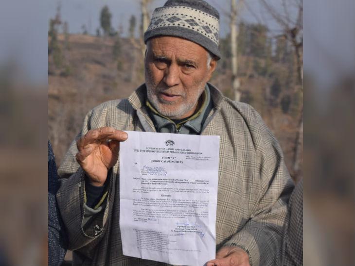 कश्मीर के बडगाम जिले के रहने वाले 62 साल के अहसान वागे सरकारी नोटिस दिखाते हुए। प्रशासन ने अतिक्रमण के नाम पर उनके सेब के पेड़ों को काट दिया है। फोटो- बसीत जरगर।