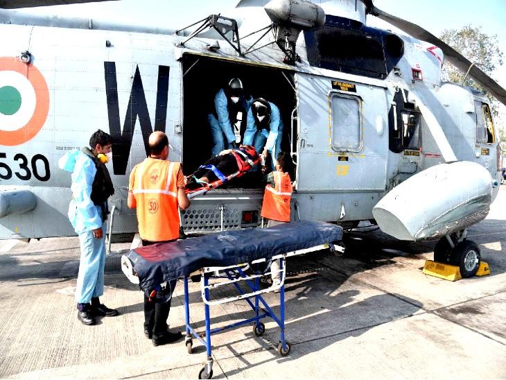 हेलिकॉप्टर से मरीज को नीचे उतारते नौसेना के जवान और मुंबई कोस्ट के कर्मचारी।