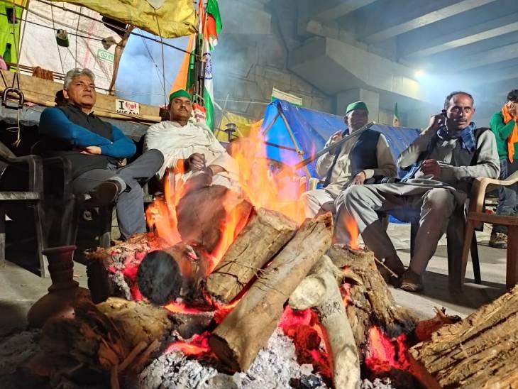 स्ट्रीट लाइट्स की दूधिया रोशनी में टेंट के बाहर किसान आग सेंक रहे हैं। कुछ किसान हुक्का भी पी रहे हैं।